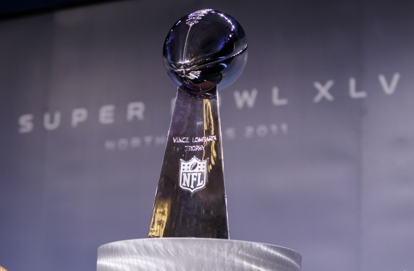 The Vince Lombardi Trophy stands between the helmets of the Pittsburgh Steelers and the Green Bay Packers at a Press Conference in Dallas